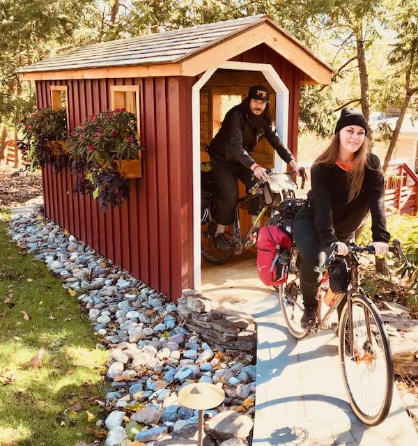 Man-Woman-biking-through-small-covered-wood-bridge-Wedgwood-backyard